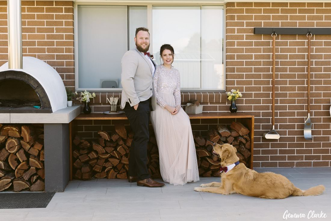 With their furbaby Barnaby and their second baby, their wood fire oven they made! A great addition for their backyard Buxton Wedding