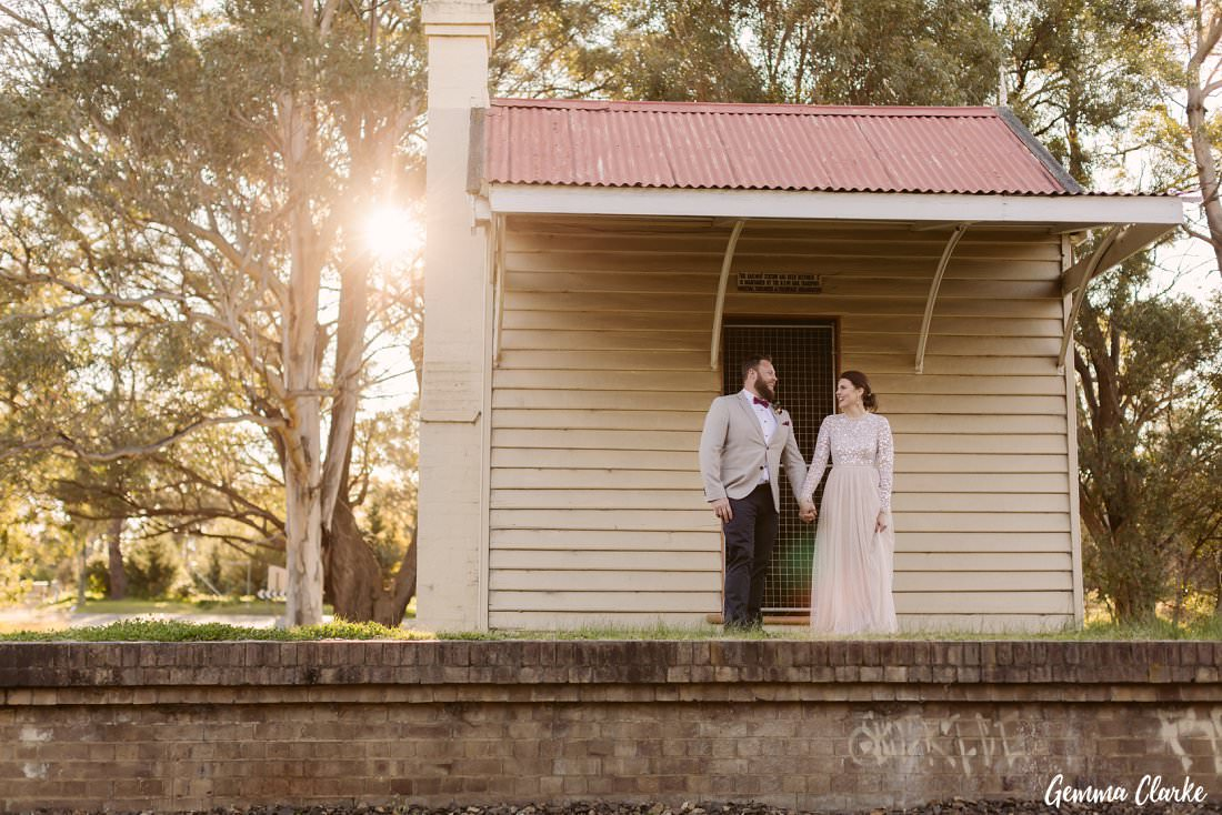 The sun was at the perfect angle to peak through the big tree at the back while the couple stand in front of the old railway station near their Buxton Wedding location