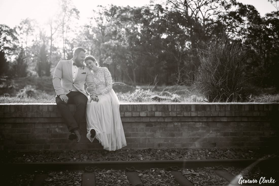 Sitting by the train tracks and having a giggle while the sun warms them up at their Buxton Wedding