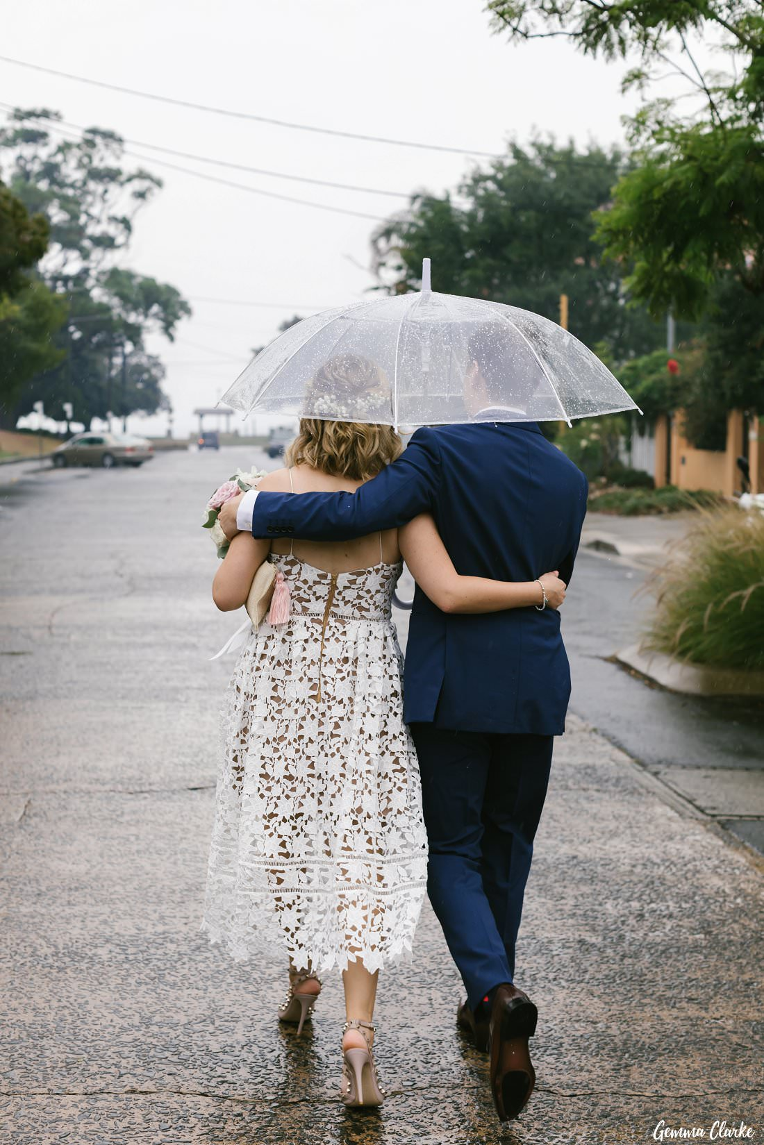 Happily walking arm and arm after they said their vows - Rain on your Wedding Day?