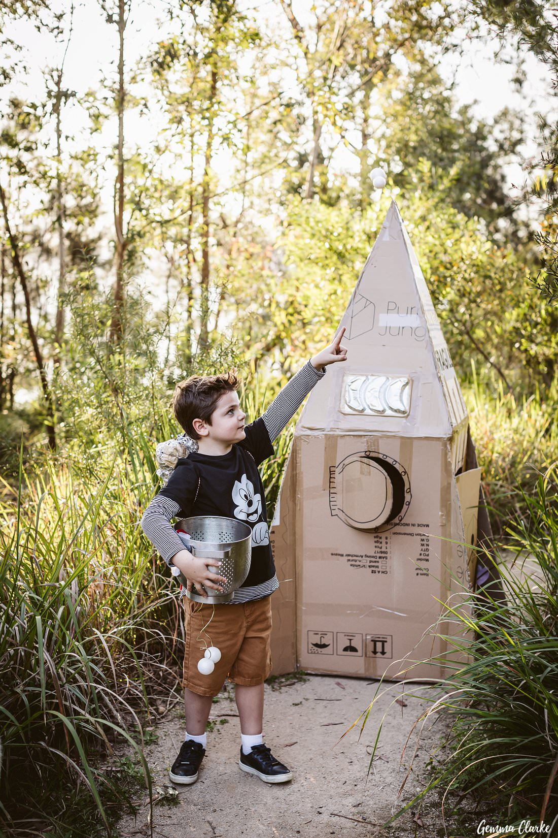 Henry holding his space helmet and in front of his amazing cardboard rocket at his space themed photo shoot