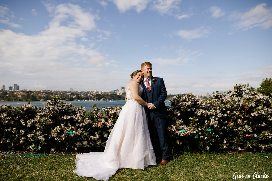 Newly married and big smiles for Fran and Jonny in front of the blooming bushes at their Cockatoo Island Elopement